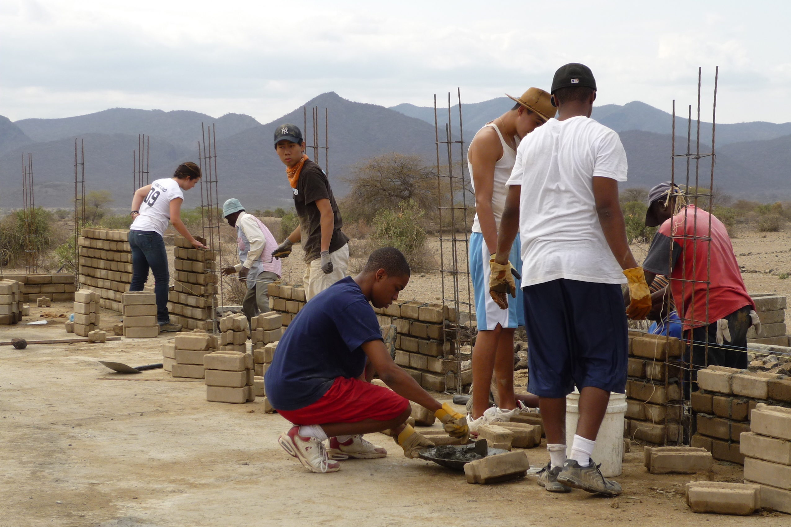 Student led work crew building compressed earth block walls in Oloika, Kenya